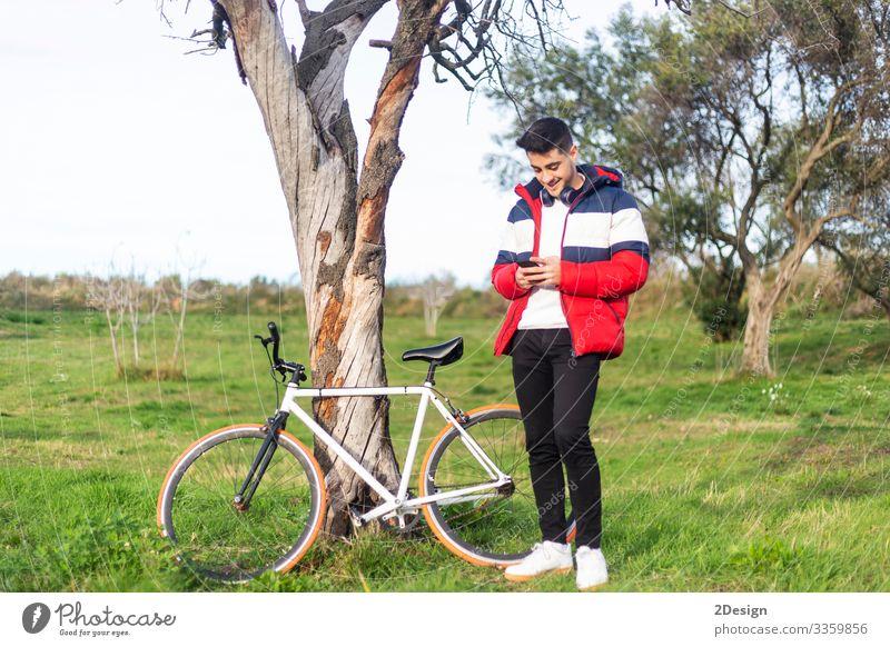Hübscher, hipper junger Mann, der eine Fahrradtour genießt und beim Spazierengehen im Park ein Smartphone benutzt Straße Menschen Telefon männlich Person laufen