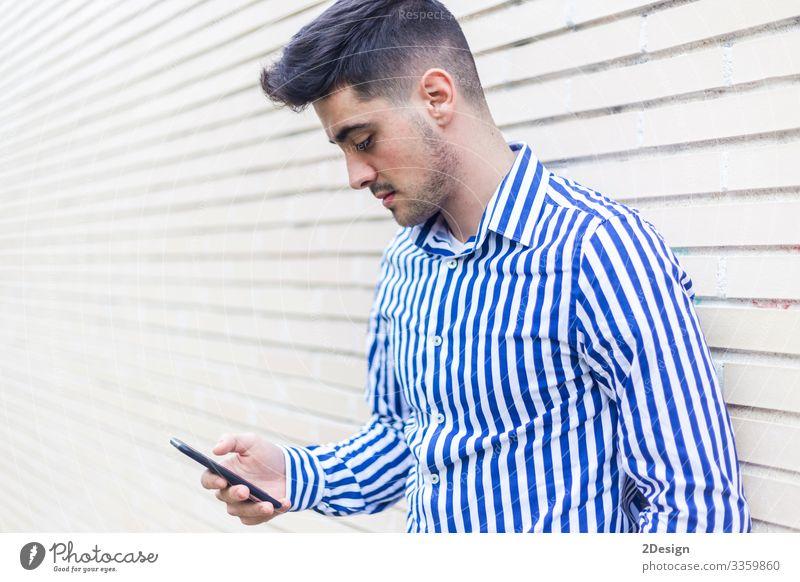Junger glücklicher Mann lehnt an Hauswand, während er sein Smartphone benutzt Lifestyle Stil Glück Business Telefon Handy PDA Technik & Technologie Mensch