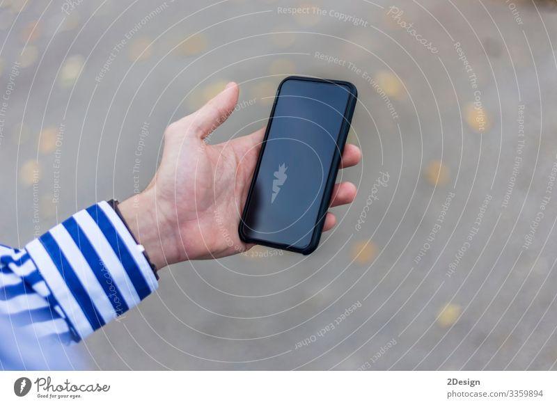 Junger Mann mit einem Smartphone in der Hand schreibt draußen auf der Straße SMS Lifestyle Telefon Handy PDA Bildschirm Technik & Technologie Mensch maskulin