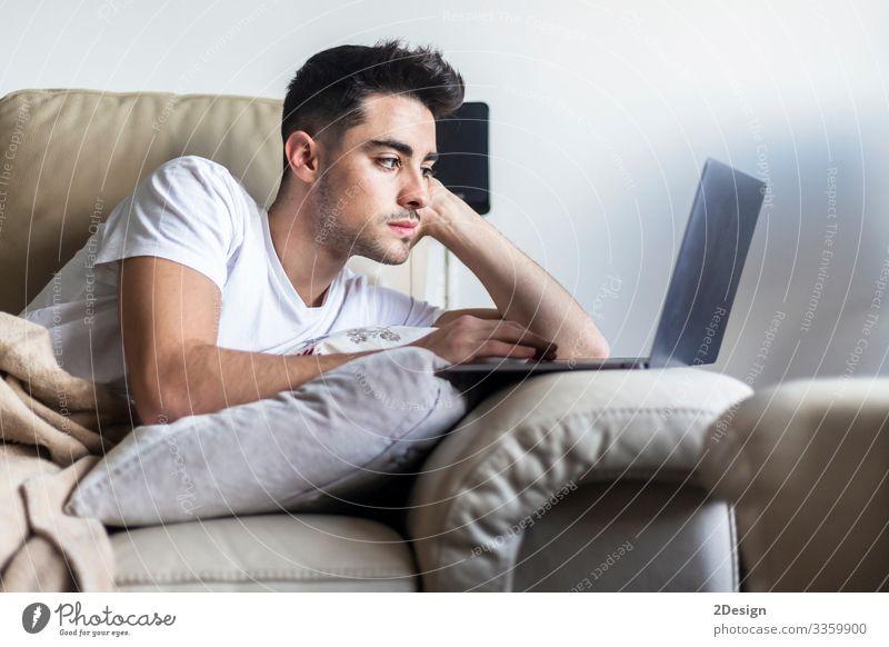 Junger Mann entspannt sich auf dem Sofa, während er den Laptop benutzt Lifestyle Glück Erholung Freizeit & Hobby Haus Wohnzimmer Arbeit & Erwerbstätigkeit