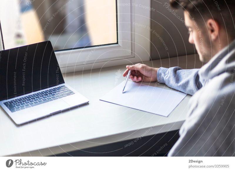 Junger bärtiger Student schreibt Notizen in einem Notizbuch Glück Leben Schreibtisch Schule lernen Studium Prüfung & Examen Arbeit & Erwerbstätigkeit