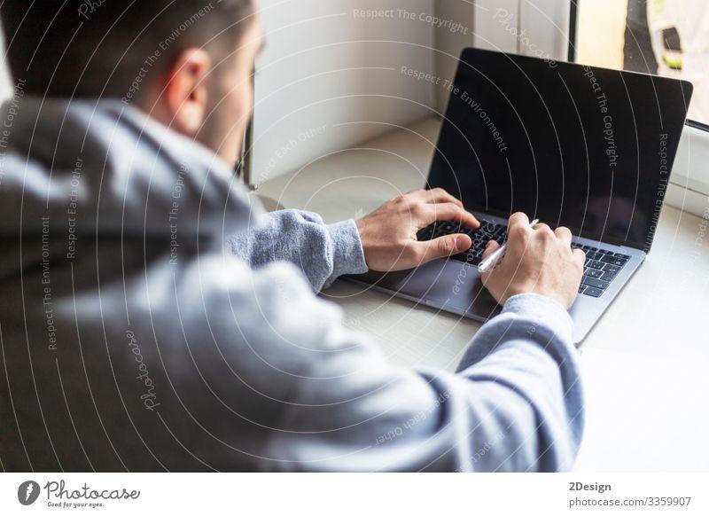 Rückansicht eines jungen Mannes, der zu Hause mit einem Laptop auf dem Desktop arbeitet Dekoration & Verzierung Schreibtisch Tisch Arbeit & Erwerbstätigkeit