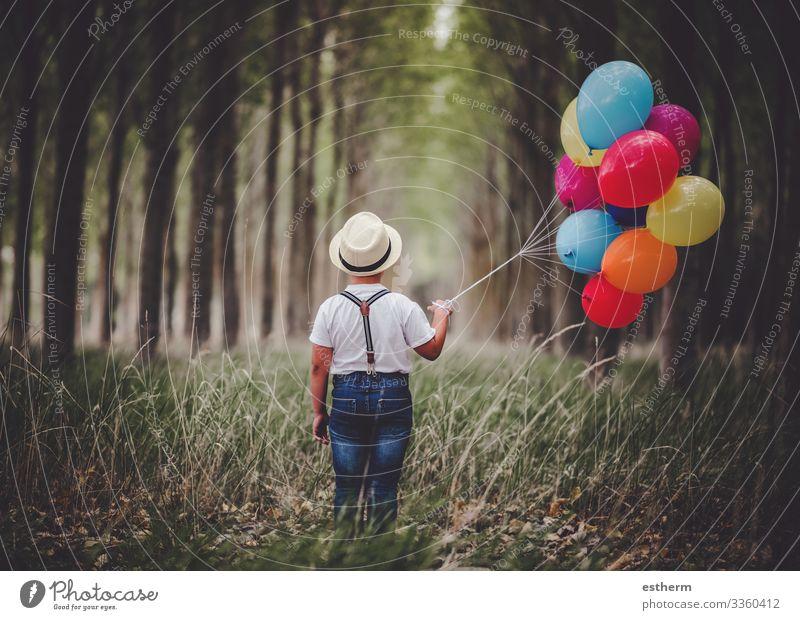 Rückansicht eines nachdenklichen Kindes mit Luftballons im Wald im Freien Lifestyle Erholung Ferien & Urlaub & Reisen Freiheit Sommer Mensch maskulin Junge