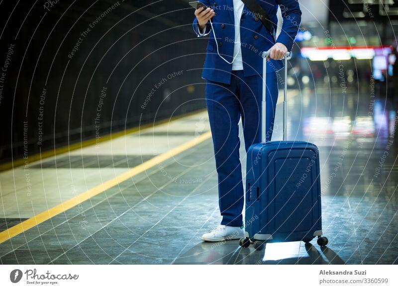 Junger, stilvoller, gut aussehender Mann im Anzug mit Koffer steht auf der Metrostation, hält ein Smartphone in der Hand, scrollt und simst, lächelt und lacht.  Vorbeifahrender Zug