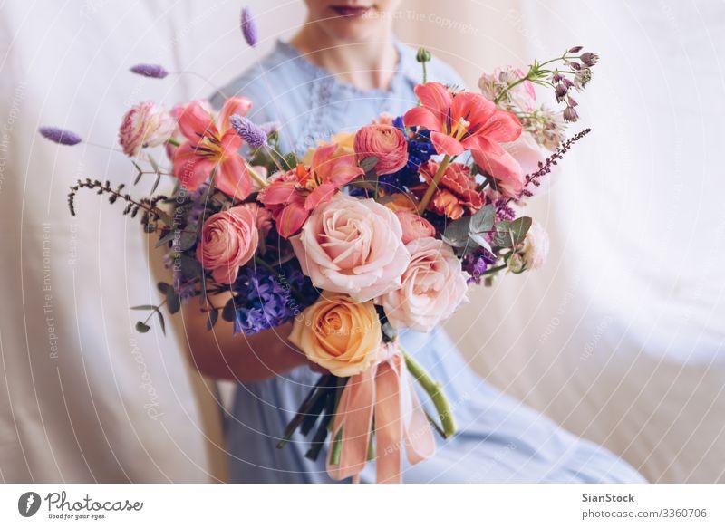 Junge Frau in einem hellblauen Kleid mit einem Blumenstrauß in der Hand. Lifestyle elegant Stil Glück schön Stuhl Hochzeit Erwachsene Lippen brünett sitzen