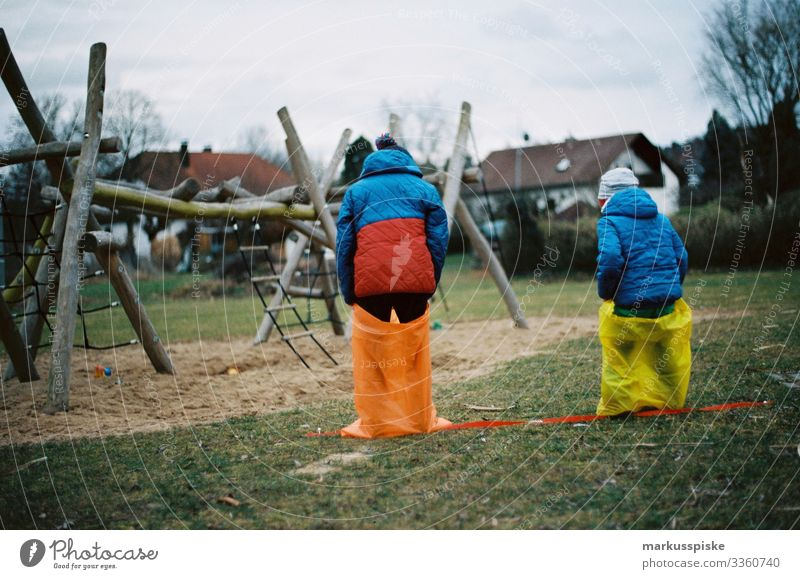 Zwei Sackhüpfen der Jungen analoge Fotografie 35mm Filmfotografie Filmscan Scan Leica R7 farbenfroh rot gelb im Freien Kind Kinder Kindheit Spielplatz