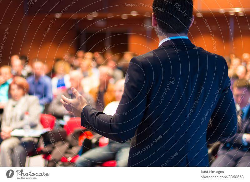 Redner auf einer Wirtschaftskonferenz mit öffentlichen Präsentationen. Publikum in der Konferenzhalle. Club für Unternehmertum. Rückansicht. Horisontale Zusammensetzung. Unscharfer Hintergrund.