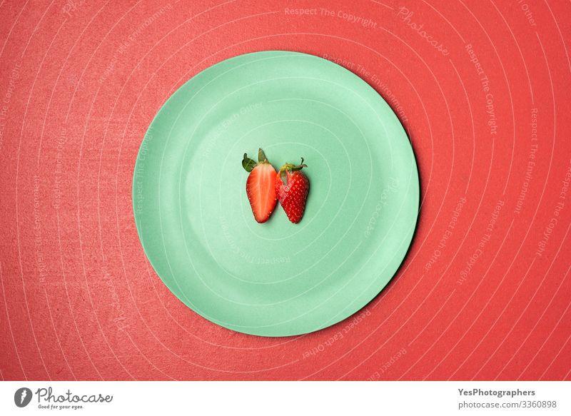 Eine halbierte Erdbeere auf grünem Teller Lebensmittel Frucht Dessert Süßwaren Ernährung Frühstück Bioprodukte lecker natürlich obere Ansicht Beeren Entwurf