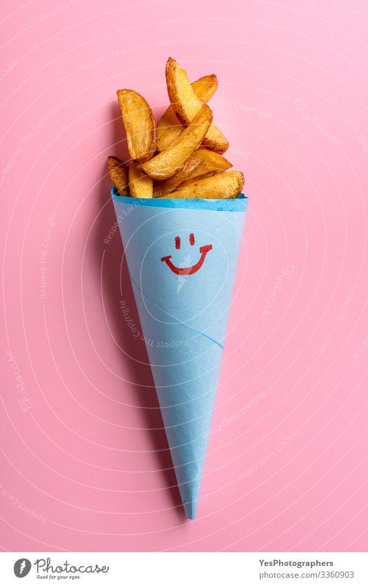 Röstkartoffeln in blauer Papiertüte auf rosa Hintergrund Lebensmittel Gemüse Abendessen Vegetarische Ernährung Fastfood lecker lustig niedlich gold