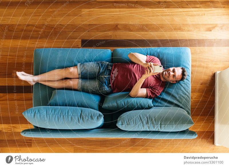 Lässiger Typ auf Sessel mit Smartphone Mann benutzend Armsessel Browsen Wohnzimmer Komfort Surfen Kälte räkeln Texten zuschauend Anschluss soziale Netzwerke