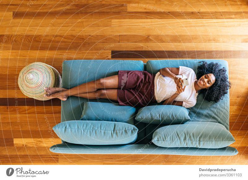 Schwarze Frau chattet auf Smartphone liegend auf Couch zu Hause benutzend Lügen Kälte räkeln Liege Sofa Wohnzimmer modern sich[Akk] entspannen Afroamerikaner