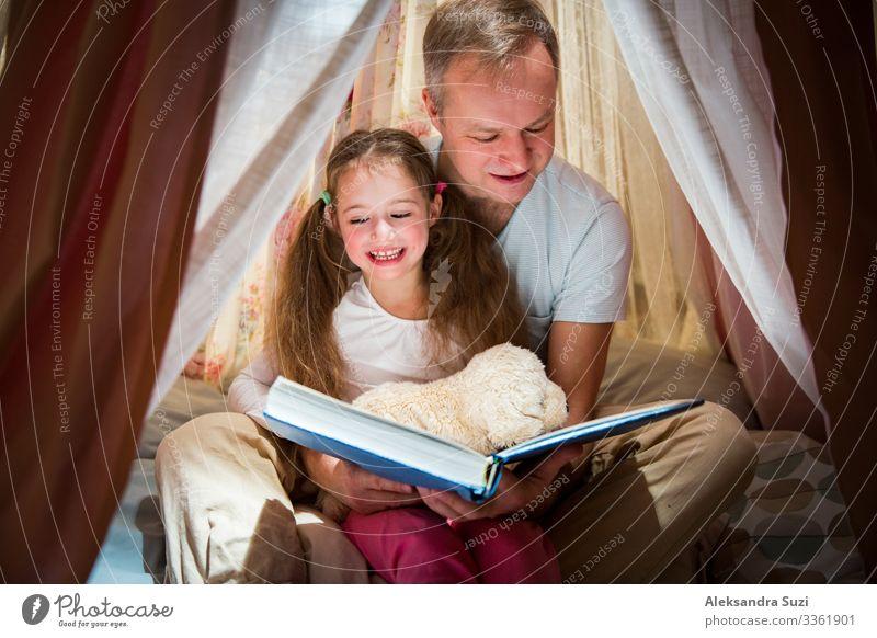 Zeit in Familienqualität. Vater und Tochter sitzen in einem selbstgebauten rosa Zelt mit Blumen, lesen ein großes Buch, sehen sich an, lächeln und lachen. Gemütliches stilvolles Zimmer. Konzept für Familienbande