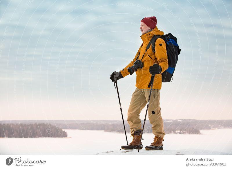 Porträt eines reifen Mannes mit grauem Bart, der Finnland im Winter erkundet. Reisender mit Kamera auf der Spitze des Felsens. Schöne Aussicht auf die nördliche Landschaft mit gefrorener Ostsee und verschneiten Inseln.