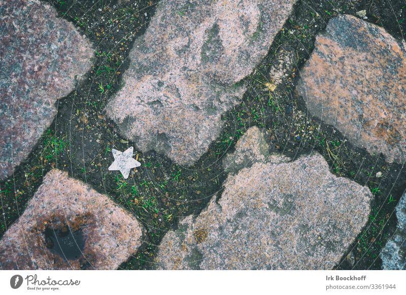 einsamer Stern auf dem Straßenpflaster Glück Stadt Wege & Pfade Zeichen Stern (Symbol) entdecken liegen positiv silber Mut Neugier Beginn Erwartung Zukunft