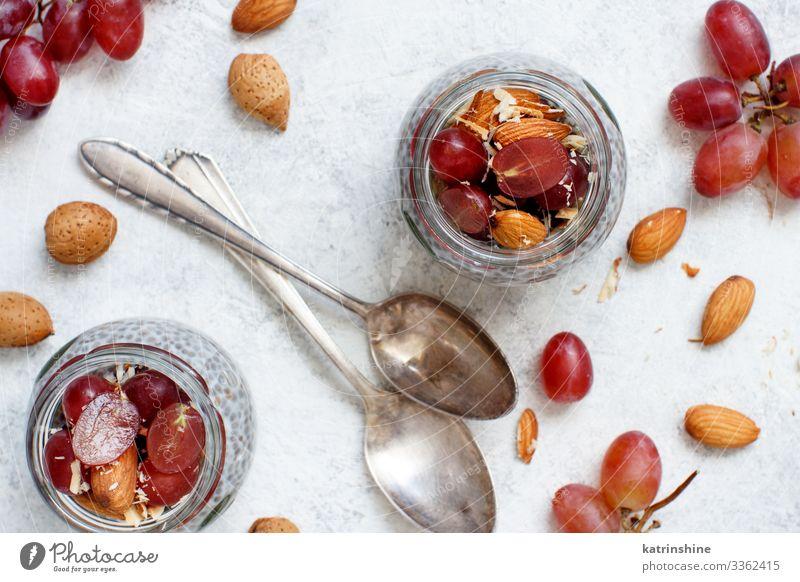 Chia-Puddingparfait mit roten Trauben und Mandeln Joghurt Frucht Dessert Essen Frühstück Diät Löffel weiß Glas Parfait Weintrauben rote Weintrauben Muttern