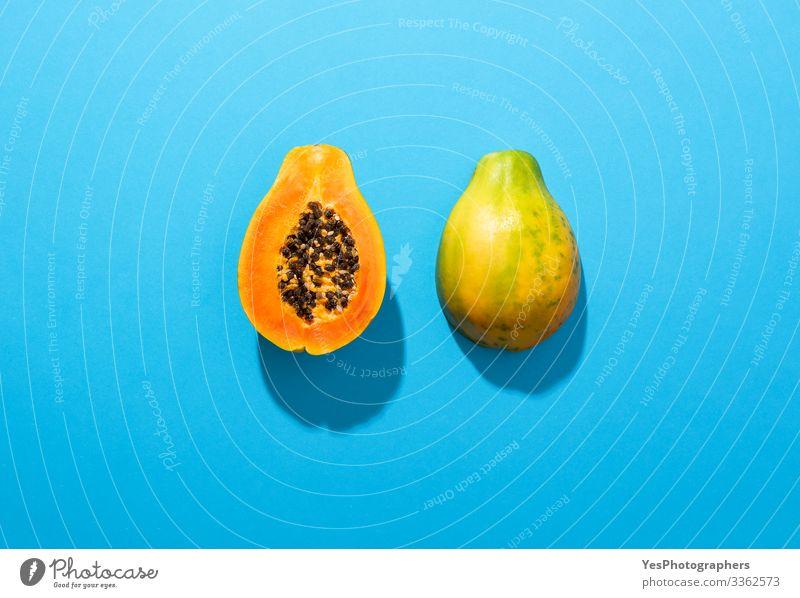 Halbierte reife Papayafrucht auf blauem Hintergrund Lebensmittel Frucht Dessert Ernährung Bioprodukte Gesunde Ernährung Duft obere Ansicht Blauer Hintergrund
