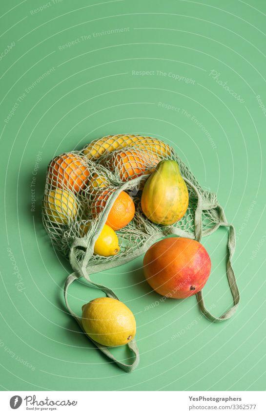 Reife tropische Früchte in einer Netz-Einkaufstasche. Früchte kaufen Frucht Orange Gesunde Ernährung grün obere Ansicht farbenfroh Diätnahrung