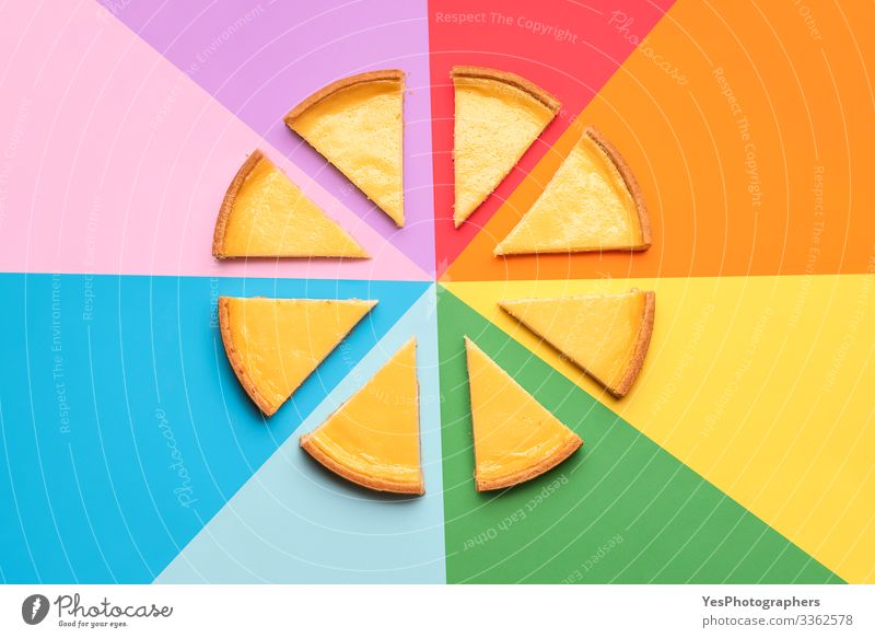 Geschnittener Käsekuchen auf einem Regenbogenhintergrund. Kuchenscheibchen Lebensmittel Milcherzeugnisse Dessert Süßwaren lecker Tradition obere Ansicht