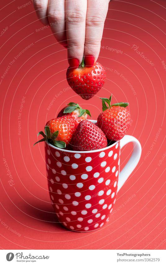 Eine reife Erdbeere von einem Haufen nehmen. Tasse Erdbeeren Lebensmittel Frucht Dessert Süßwaren Ernährung Frühstück Bioprodukte Becher Gesunde Ernährung