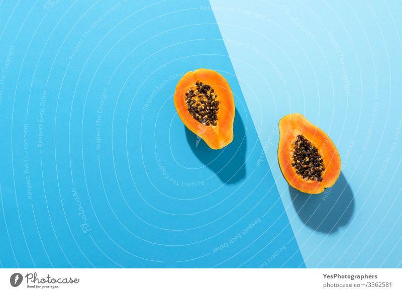 Frische Papayafrüchte halbiert auf blauem Hintergrund Frucht Dessert Bioprodukte Gesunde Ernährung saftig obere Ansicht Blauer Hintergrund blaue Farbtöne