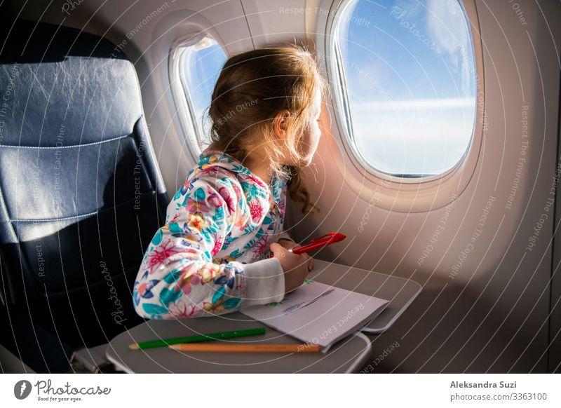 Kind malt ein Bild mit Buntstiften im Flugzeug Abenteuer Luftverkehr Flugzeuglandung Ankunft langweilig Aktion Hütte Kindheit Farbe Farbstift Abheben