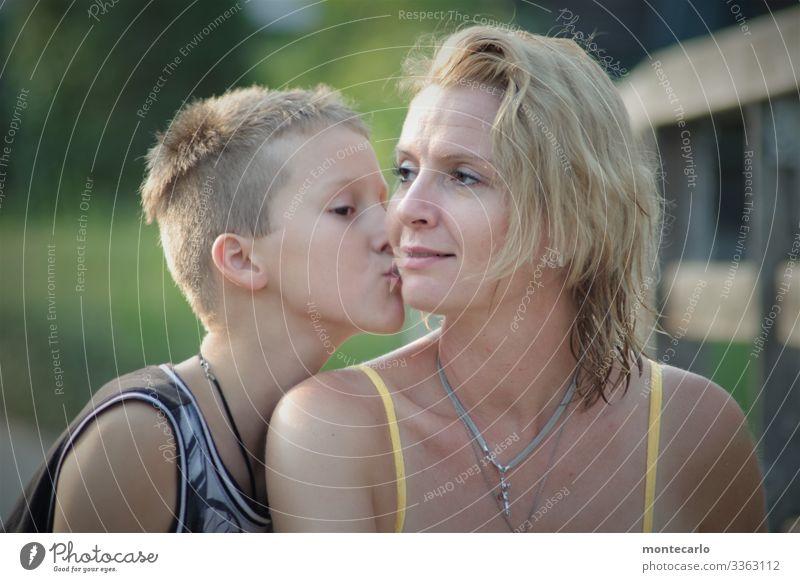 Sohn küßt seine Mutter auf die Wange Familie Junge Frau Vertrauen Zufriedenheit Sicherheit Geborgenheit loyal Schutz Liebe ruhig Farbfoto authentisch Tag