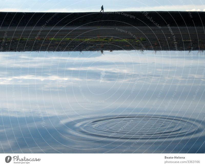 Spaziergänger am Wasser hinter gespiegeltem Himmel mit Wasserkreis Spaziergang Kai Ufer Wasserspiegelung Wasserkreise Natur blau See Reflexion & Spiegelung