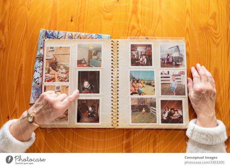 Draufsicht einer älteren kaukasischen Frau, die sich ein altes Fotoalbum anschaut Themen von Erinnerungen Nostalgie Fotos im Ruhestand Senior Album Bild Ehefrau