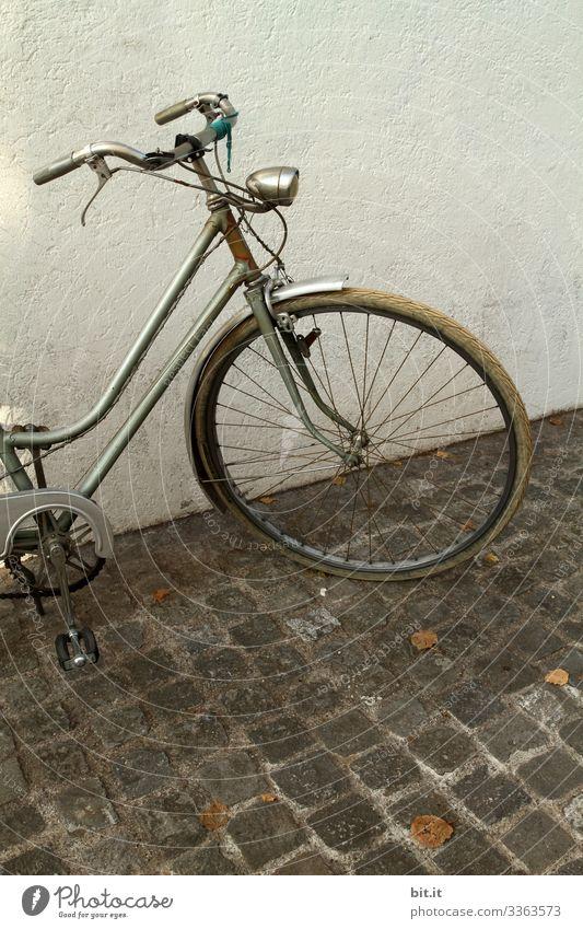 alt l altes, nostalgisches Rad im Retro-Stil, steht geparkt vor weisser, heller Hauswand auf Kopfsteinpflaster. Vorderteil, Lenker, Lampe, Licht, Reifen, Bremse von grauem Rad parkt in der Stadt. Diebstahlgefahr von altem Fahrrad, nicht abgeschlossen.