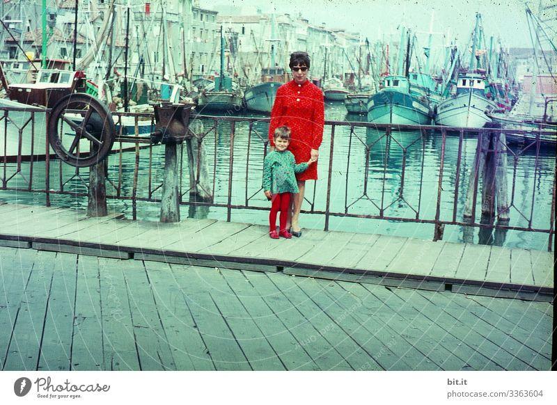 Glückliche, modische, stylische Mutter mit Tochter an der Hand, im Partnerlook, stehen im Urlaub in den 60 er Jahren, während einem Stadtbummel; Ausflug auf einer Brücke im Hafen von Venedig, mit Wasser, Schiffen und Booten im Hintergrund.