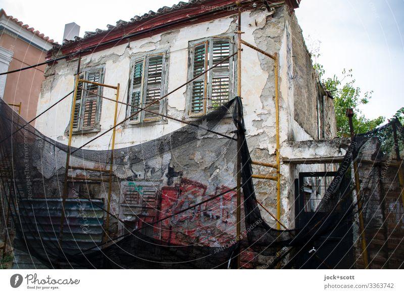 Abbruchhaus mit Netz abgesichert Sicherheitsnetz Schutz Himmel Fassade Gerüst Baugerüst Fenster Architektur Totale Starke Tiefenschärfe Sonnenlicht Kontrast