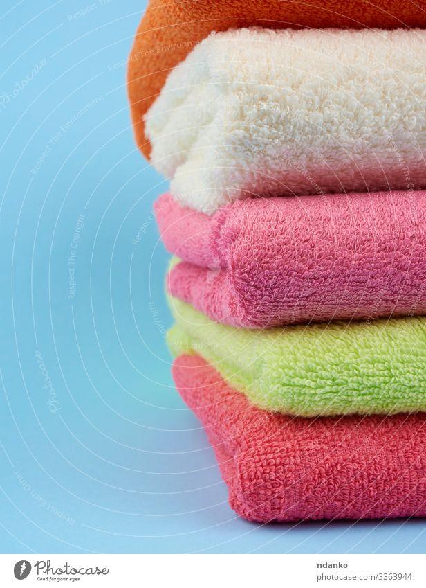 gefaltete Handtücher aus farbigem Baumwollfrottee Lifestyle Design Körper Erholung Spa Massage Bad Stoff frisch neu Sauberkeit weich blau grün rosa weiß Farbe