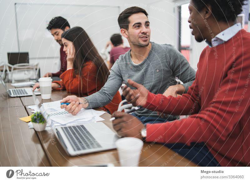 Junge kreative Designer, die in einem Projekt arbeiten und die Entwicklung einer neuen Ordnung am Arbeitsplatz diskutieren. Geschäftskonzept. Tisch