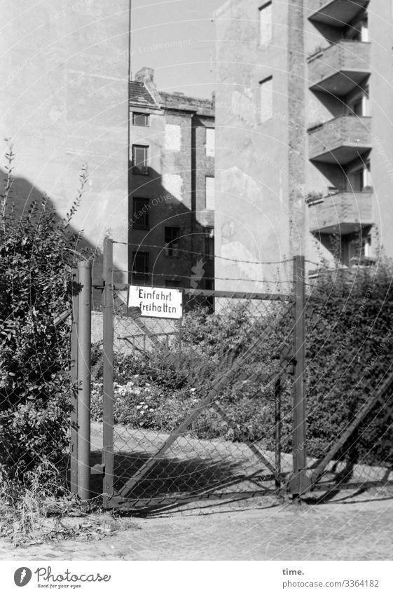 Geschichten vom Zaun (101) zaun einfahrt schild freihalten tor häuser hochhäuser hinterhof verschlossen hecke gebüsch fassade mauer sonnig schatten stacheldraht