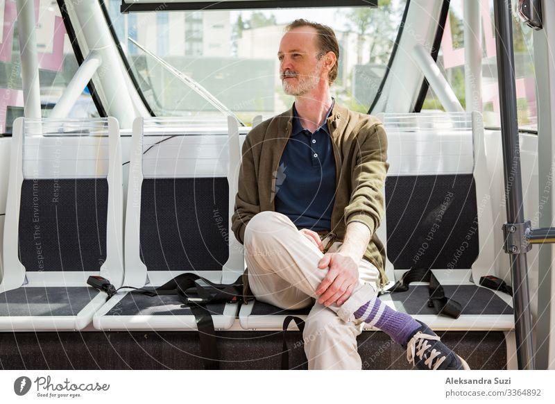 Innenansicht eines automatischen ferngesteuerten Busses in Helsinki. Unbemannter Test des öffentlichen Verkehrs auf der Straße. Fahrgast sitzt auf dem Sitz und wartet an der Bushaltestelle.