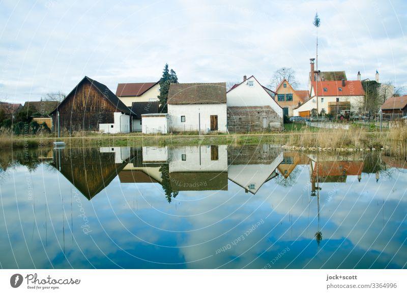 Ländliche fränkische Häuser an einem idyllischen Teich gelegen die sich in ihm spiegeln Franken Karpfenteich ländlich Schönes Wetter Himmel Wolken Landschaft