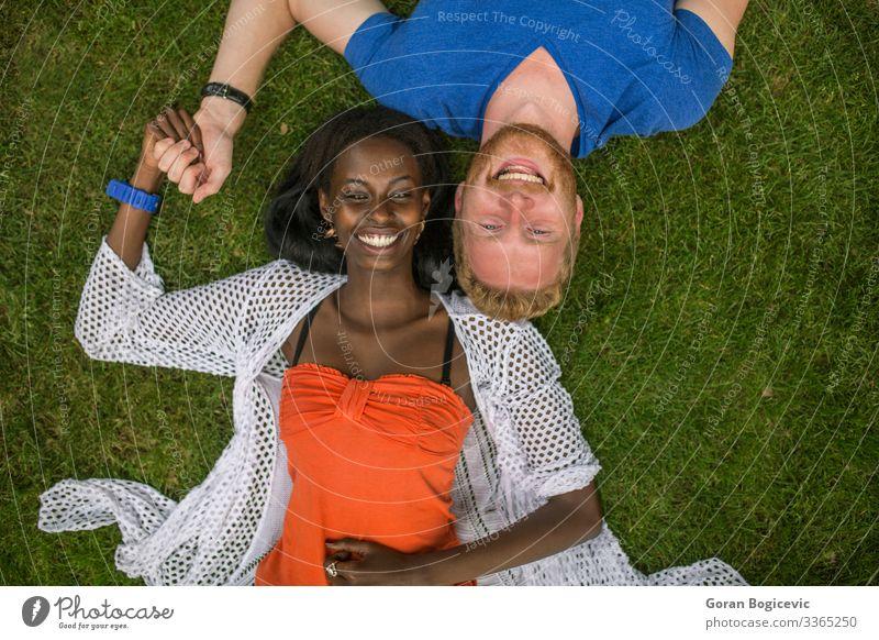 Mehrrassiges Paar im Park Lifestyle Sommer Mensch Junge Frau Jugendliche Junger Mann Erwachsene 2 18-30 Jahre Gras rothaarig Zusammensein modern Freund lässig