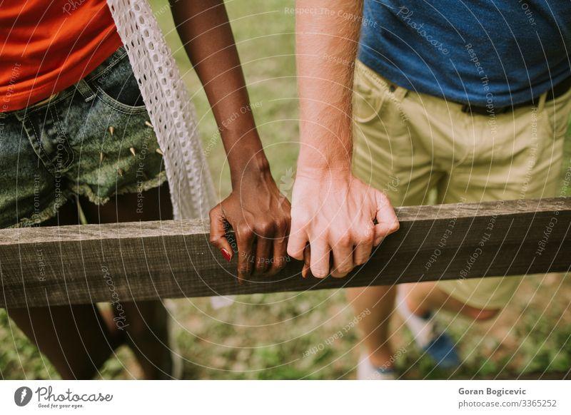 Mehrrassiges Paar im Park Lifestyle Sommer Mensch Frau Erwachsene Mann Arme Hand Holz Zusammensein modern schwarz Freund lässig Kaukasier Vielfalt Zaun aus Holz