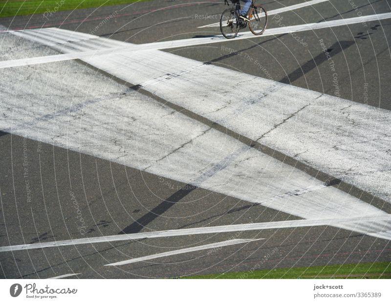Radfahrer erscheint auf der Linie vom Flugplatz Doppelbelichtung Linien Experiment Landebahn Mobilität Freizeit Strukturen & Formen Freizeit & Hobby