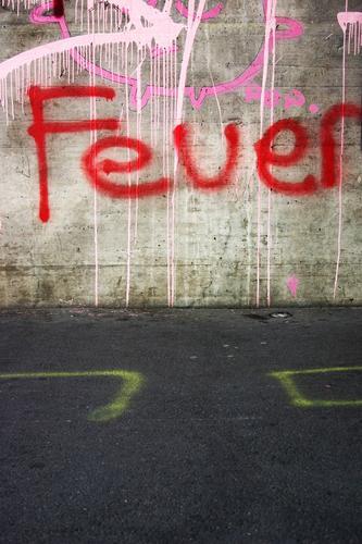 Schriftzug Feuer, steht in Rot geschrieben, auf einer grauen Wand aus Beton, an einer Straße. Brand brennen Flamme heiß Grill Menschenleer rot Brennholz Rauch