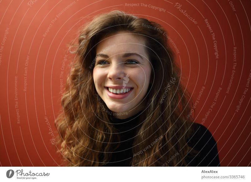 Portrait einer lächelnden, jungen Frau mit Grübchen vor einer roten Wand elegant Freude schön Leben Wohlgefühl Wohnung Junge Frau Jugendliche Gesicht