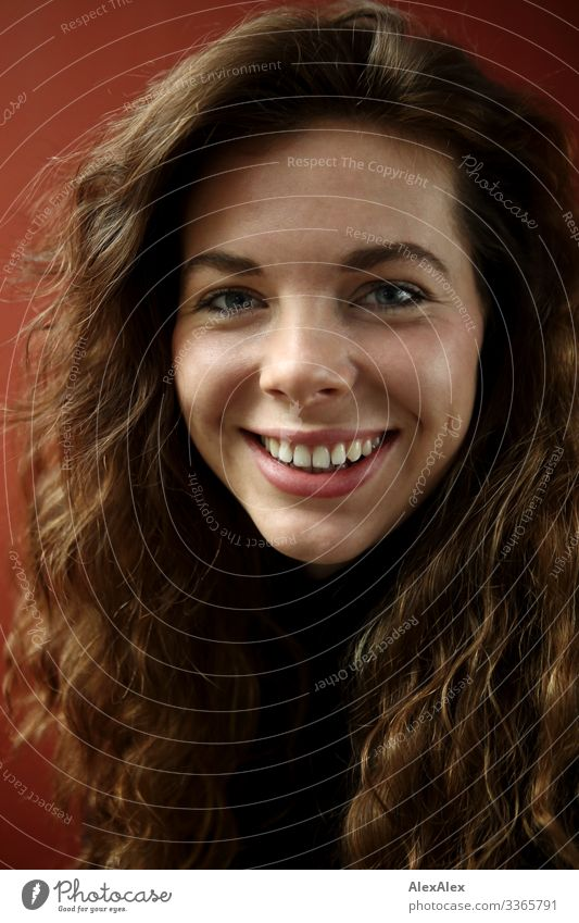 Portrait einer lächelnden, jungen Frau mit Grübchen vor einer roten Wand Lifestyle Stil Freude schön Leben Junge Frau Jugendliche Haare & Frisuren Gesicht