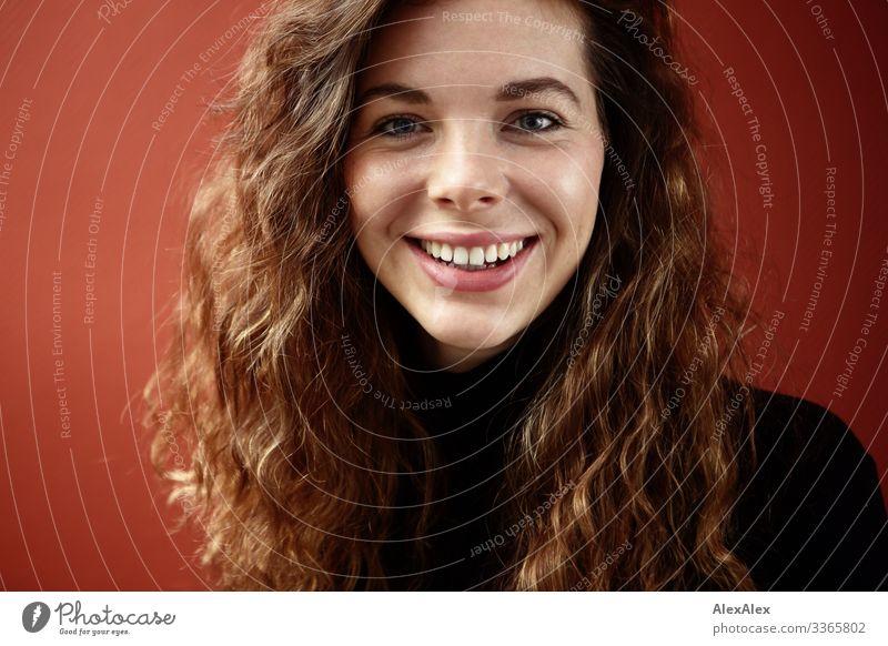 Portrait einer lächelnden, jungen Frau mit Grübchen vor einer roten Wand Häusliches Leben Junge Frau Jugendliche Gesicht 18-30 Jahre Erwachsene Pullover brünett