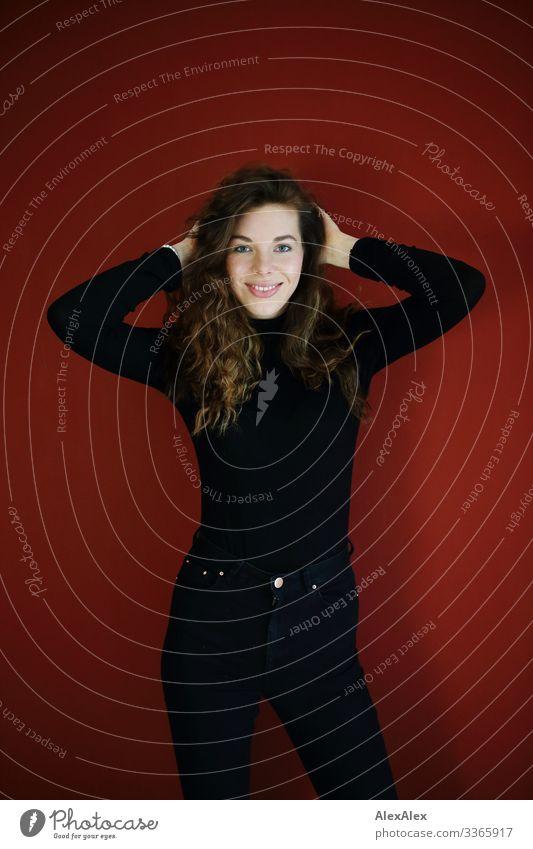 Junge, große, lächelnde Frau vor roter Wand Lifestyle elegant Stil Freude schön Leben Wohnung Raum rote Wand Junge Frau Jugendliche 18-30 Jahre Erwachsene