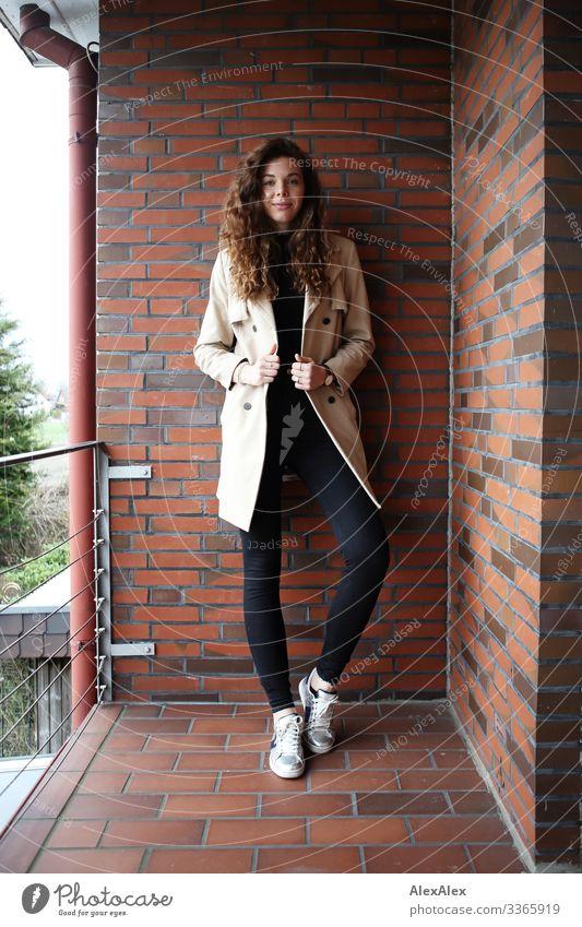 Junge, große Frau steht auf einem Balkon mit Ziegelsteinmauer Lifestyle Stil Freude schön Leben Häusliches Leben Junge Frau Jugendliche 18-30 Jahre Erwachsene