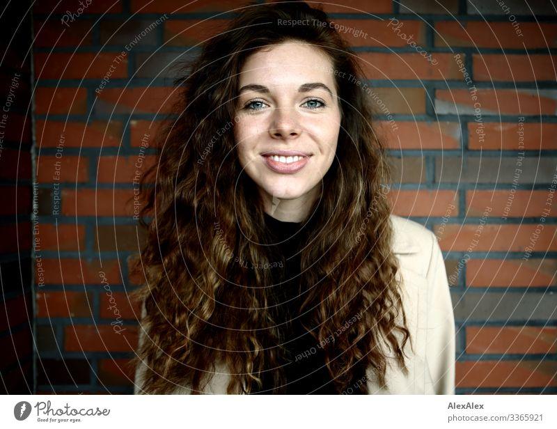 Portrait einer jungen Frau vor einer Ziegelsteinwand Lifestyle Stil Freude schön Leben Junge Frau Jugendliche Gesicht 18-30 Jahre Erwachsene Mantel brünett