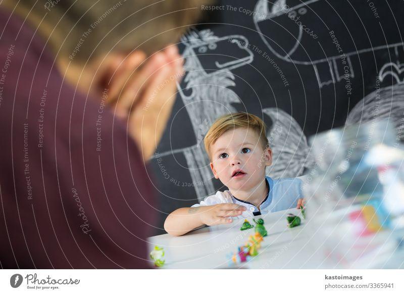 Süßes Kleinkind bei der Kindertherapiesitzung. Spielen Tisch Entertainment Lehrer Junge Mann Erwachsene Kindheit Spielzeug sitzen niedlich Gefühle Idee Kontakt