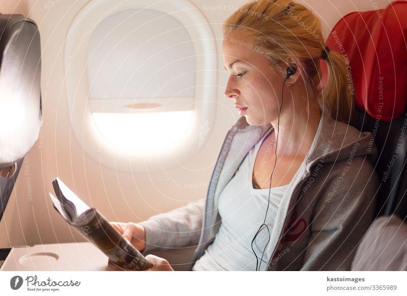 Frau, die eine Zeitschrift liest und im Flugzeug Musik hört. Lifestyle Erholung lesen Ferien & Urlaub & Reisen Ausflug Entertainment Wirtschaft Business Mensch