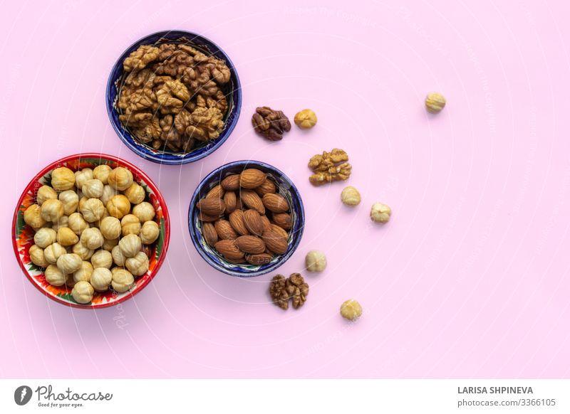 Sortimentsmix aus Nüssen in Schalen auf rosa Gemüse Ernährung Vegetarische Ernährung Diät Teller Schalen & Schüsseln Tisch Menschengruppe natürlich oben Verfall