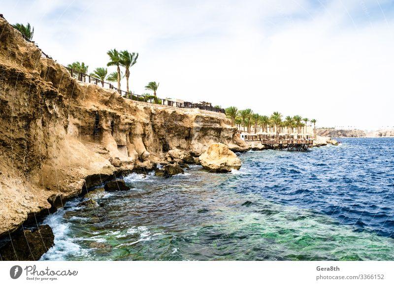 Blick vom Meer auf einen Felsstrand und ein Riff am Roten Meer Ferien & Urlaub & Reisen Wellen Himmel Küste Korallenriff Stein blau gelb Ägypten Rotes Meer
